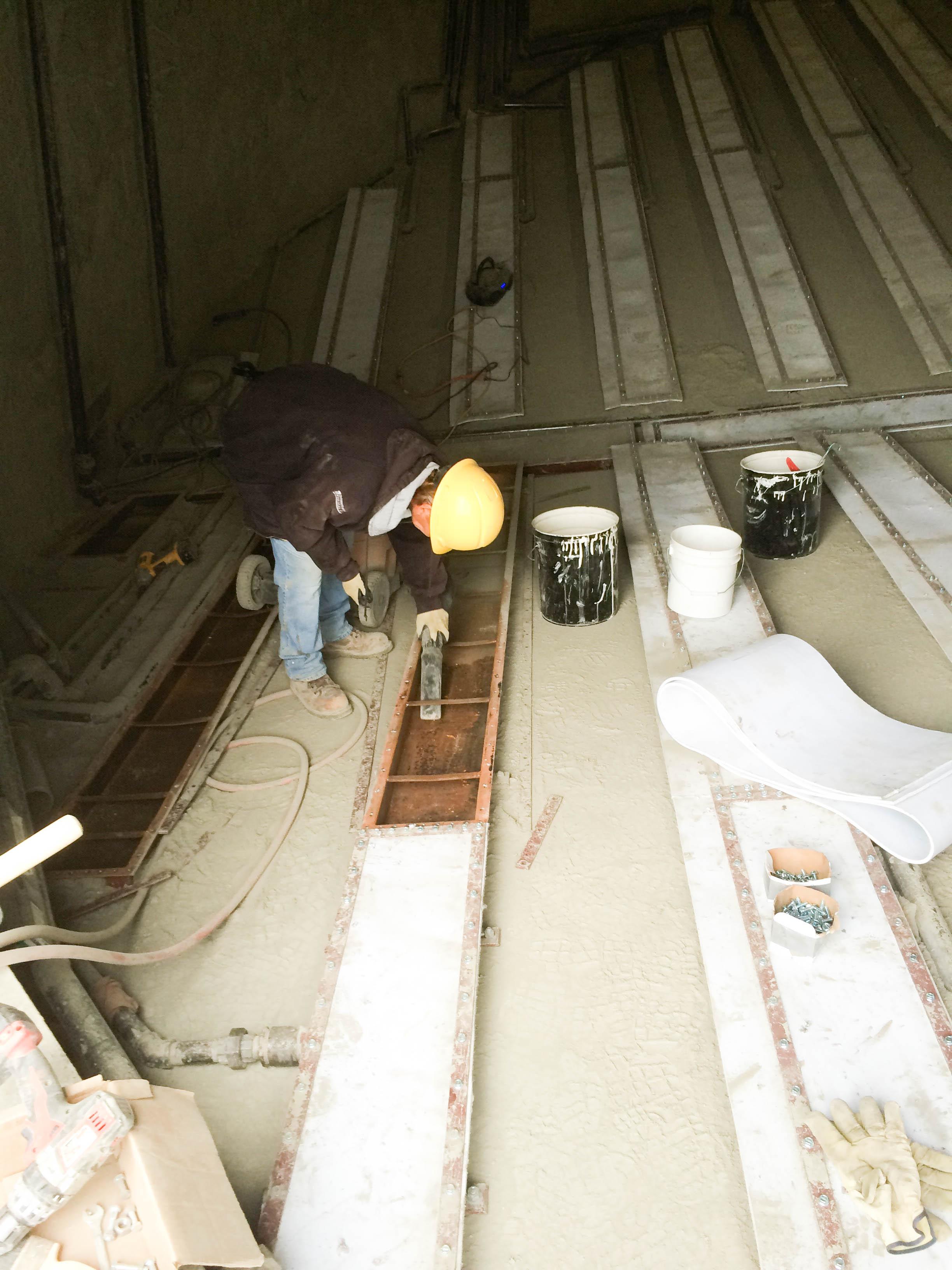 Men adding silo coating to silo