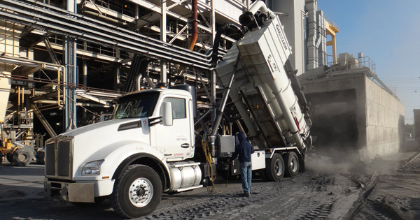 Vacuum truck pouring material from silo cleaning